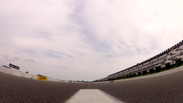 Low angle view from race track as three stock cars rumble over the camera towards the finish line.