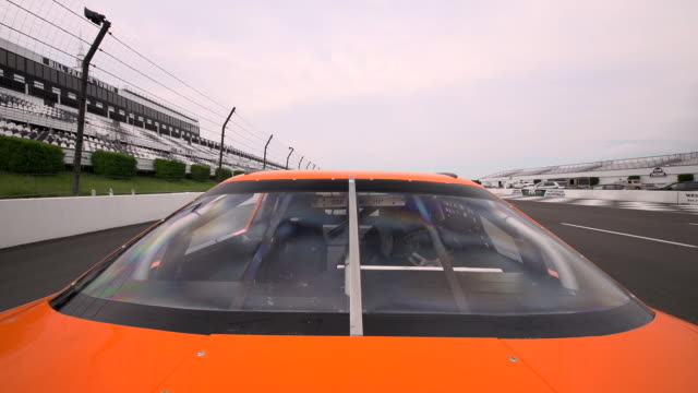 Low angle view from race track as three stock cars speed past.