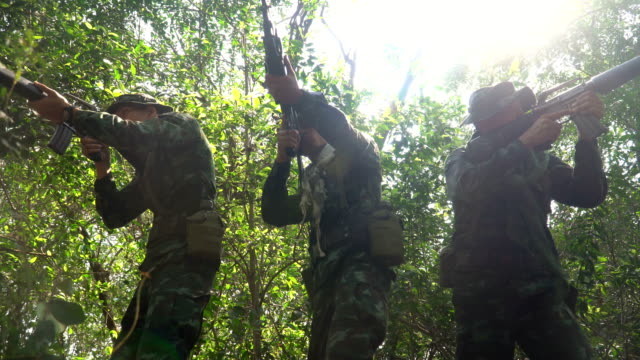low angle view: gesture of three fully Equipped and armed Soldiers is ready to fight