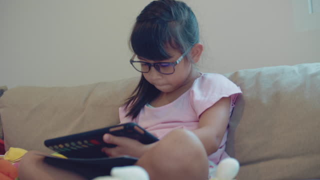 [low angle view] girl playing game on tablet - girl cross legged stock videos & royalty-free footage