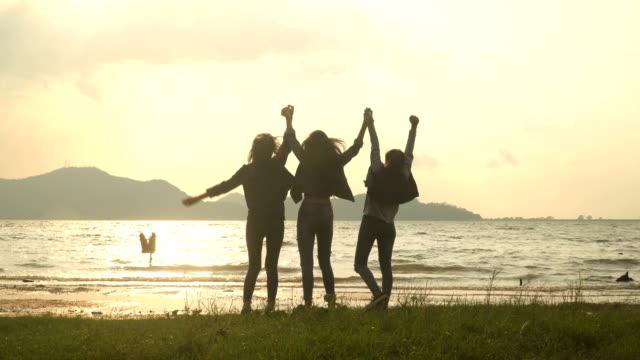 低角度ビュー: 水辺で美しい夕日の眺めに腕を上げるために走っている若い女性のグループ