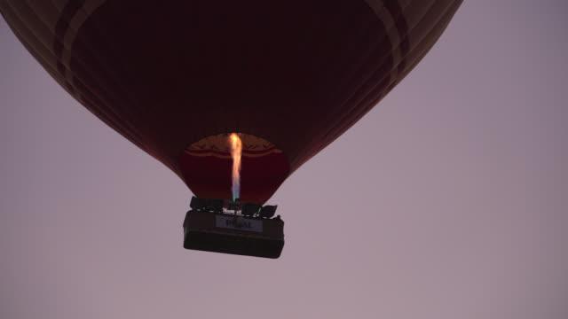 stockvideo's en b-roll-footage met lage hoek weergave: hete luchtballonnen beginnen vliegen bij zonsopgang, cappadocië, turkije - donker beeld