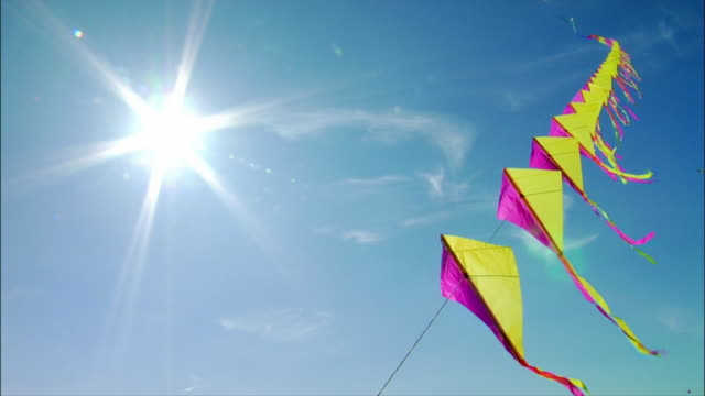 low angle view. large group of kites flying in the wind. - kite toy stock videos and b-roll footage