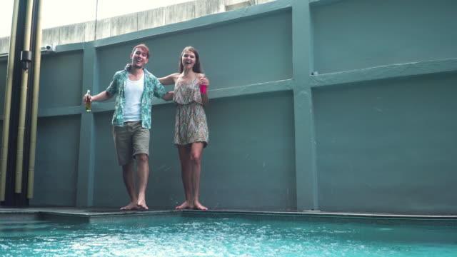blick in die tiefe: multiethnische freunde, die freizeitaktivitäten mit fröhlichem gefühl während ihres urlaubs in einem luxushotel haben, stehend und mit wasser in der nähe von pool oder schwimmbad und spielgenuss. konzept eines strandurlaubs und ges - freibad stock-videos und b-roll-filmmaterial