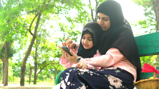 low angle view: muslim girl using smartphone with her mother on bench in public park in morning - teaching stock videos & royalty-free footage