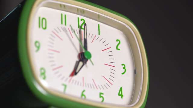 low angle view of a bright green analogue alarm clock - 秒針点の映像素材/bロール