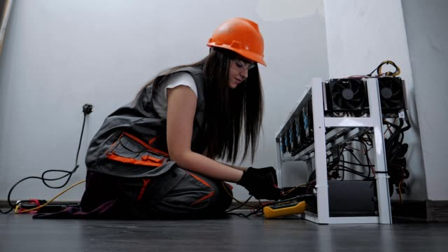 Low Angle View of a Female Electrician Working on an IT item, Engineering, Measuring Electrical Resistance, Professional IT Support, Technology, STEM, Experienced Professional