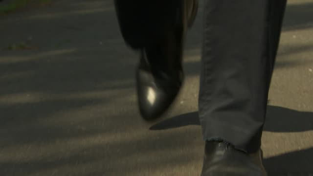 low angle view of a man in smart shoes walking down a road - men stock videos & royalty-free footage