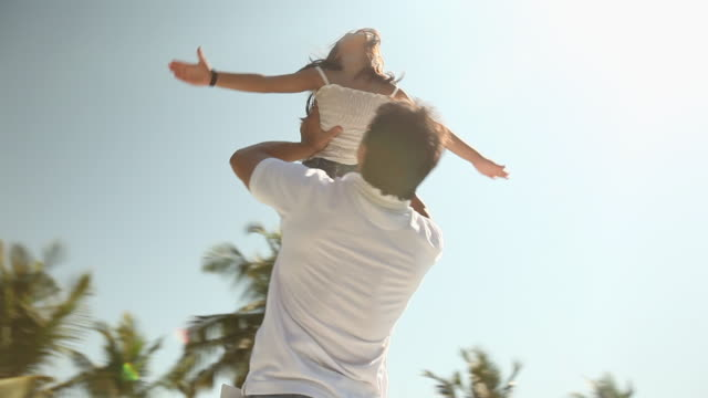 Low angle view of a man playing with his daughter in a park