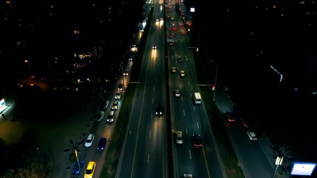vídeos y material grabado en eventos de stock de vista de ángulo bajo de un revelador tiro aéreo ciudad de luces de tráfico en la noche - alto descripción física