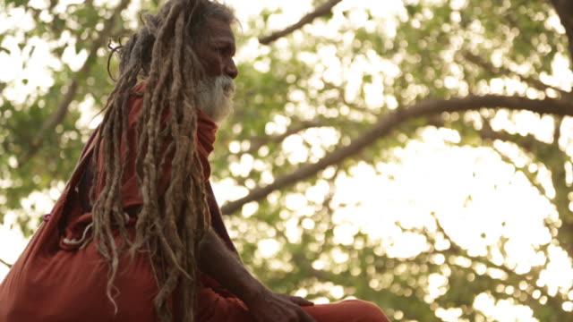 vídeos de stock, filmes e b-roll de low angle view of a sage worshipping, rishikesh, uttarakhand, india - rishikesh
