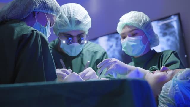 low-winkel-ansicht eines chirurgen trägt binokulare lupe arbeiten, um ihr leben der asiatischen patientin, die auf einem bett in einem operationssaal im krankenhaus zu retten, um das leben zu verlängern zu retten.  hilfe bei der frau mit dem monitor von  - 20 29 years stock-videos und b-roll-filmmaterial