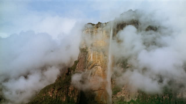Low angle view of Angel Falls down side of cliff obscured by clouds / Canaima National Park, Venezuela