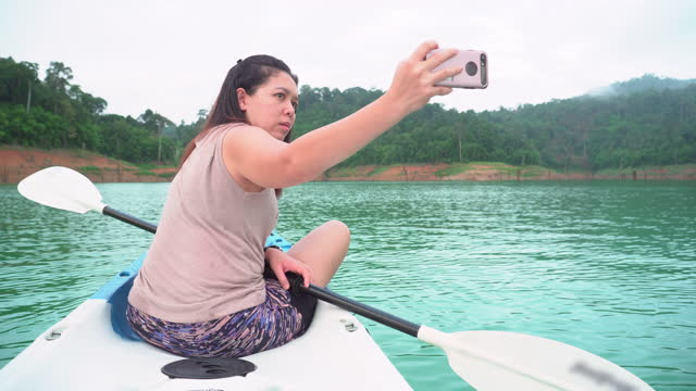 low angle view of asian woman using a smartphone to take photos, selfies, taking relaxation among natural blue khao sok lake with outdoor activities, padding with kayak in summer holiday vacation. - natural black hair stock videos & royalty-free footage