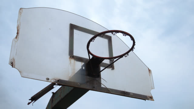 vídeos de stock, filmes e b-roll de opinião de baixo ângulo da aro de basquetebol sem rede ao ar livre - pátio de escola
