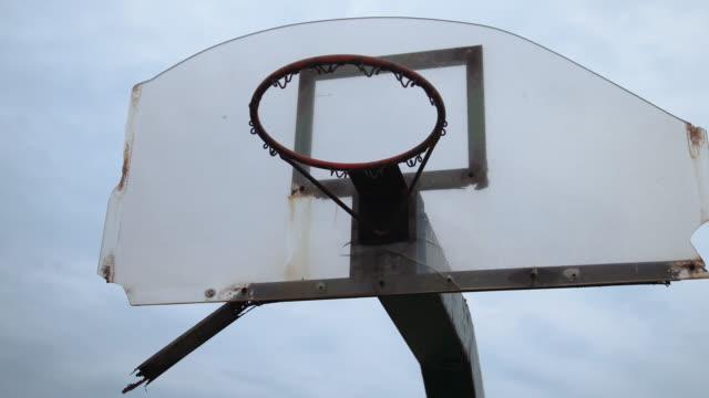 vídeos de stock e filmes b-roll de low angle view of basketball hoop without net outdoors - quadra desportiva