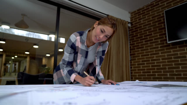 Low angle view of beautiful woman working on a business plan looking very focused