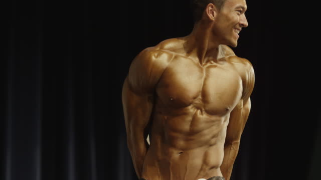 vídeos de stock e filmes b-roll de low angle view of bodybuilders posing on stage at competition / draper, utah, united states - body building