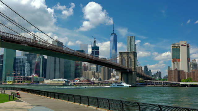 low angle view of brooklyn bridge over east river by cityscape against sky - brooklyn bridge stock videos & royalty-free footage