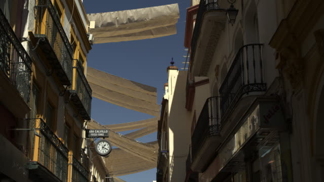 low angle view of canopies over street between buildings / seville, sevilla, spain - spain stock videos & royalty-free footage