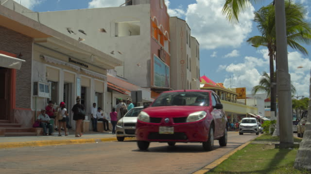 low angle view of cars and motorcycle driving on waterfront street / cozumel, quintana roo, mexico - cozumel stock videos and b-roll footage