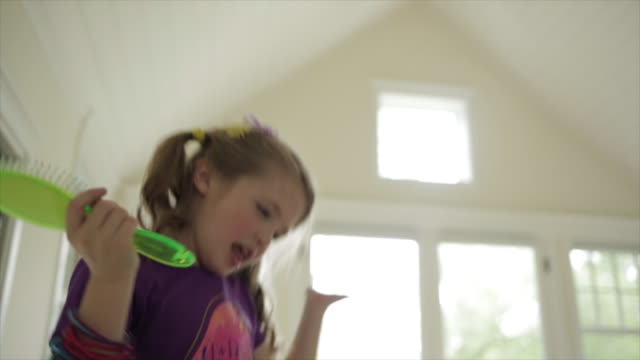 Low angle view of cheerful girl dancing at home