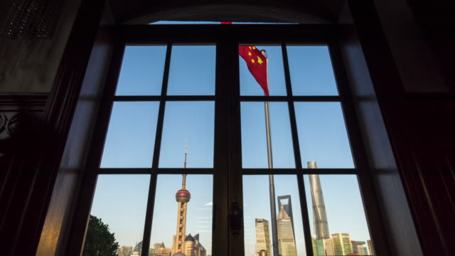 low angle view of chinese national flag in front of landmark shanghai cityscape - communism stock videos & royalty-free footage