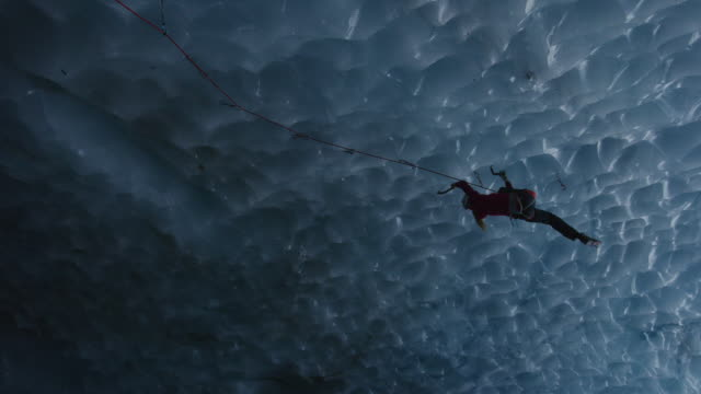 low angle view of climber in ice cave using rope and hooks / palmer, alaska, united states - höhle stock-videos und b-roll-filmmaterial