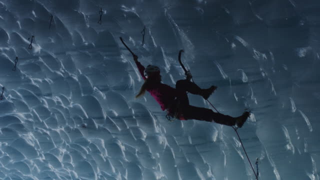 low angle view of climber in ice cave using rope and hooks / palmer, alaska, united states - schützen stock-videos und b-roll-filmmaterial