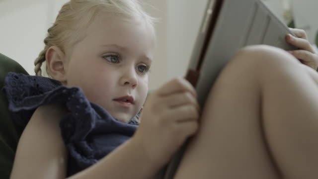 vidéos et rushes de low angle view of close up of girl reading digital tablet / cedar hills, utah, united states - langue humaine