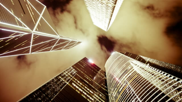 low angle view of clouds moving over tall office buildings including the bank of china, central, hong kong, china, time-lapse - bank of china tower hong kong stock videos & royalty-free footage