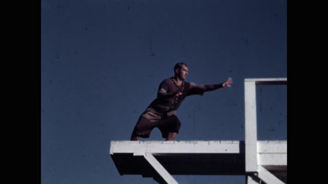 low angle view of clown diver looking at lake from diving platform - diving platform stock videos & royalty-free footage