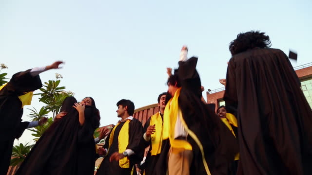 low angle view of college students celebrating graduation day in the college  - graduation stock videos and b-roll footage