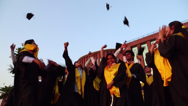 low angle view of college students celebrating graduation day in the college  - 帽子点の映像素材/bロール