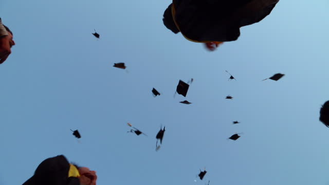 low angle view of college students celebrating graduation day in the college  - hat stock videos & royalty-free footage