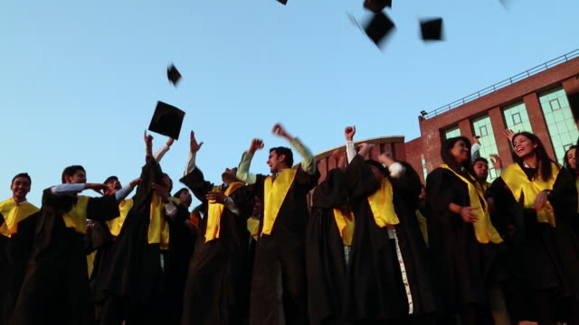 stockvideo's en b-roll-footage met low angle view of college students celebrating graduation day in the college  - universiteitsstudent