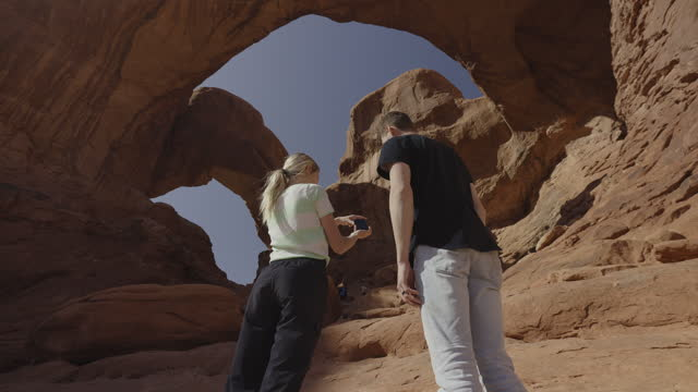 low angle view of couple photographing rock formation / moab, utah, united states - utah stock videos & royalty-free footage