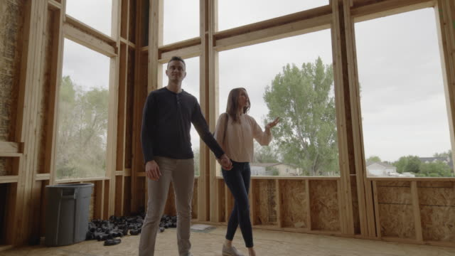 low angle view of couple talking and pointing in interior of home under construction / pleasant grove, utah, united states - three quarter length stock videos & royalty-free footage