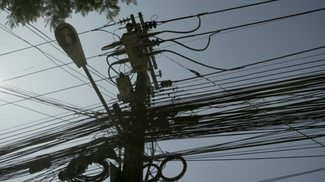 low angle view of electricity pylon against clear sky during sunny day - chiang rai, thailand - transformer stock videos & royalty-free footage
