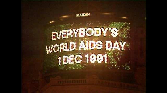 low angle view of electronic screen display at piccadilly circus, london, during world aids day; december 1991. - commercial sign stock videos & royalty-free footage