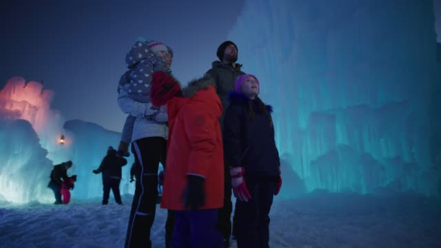 low angle view of family looking at ice castle at night / midway, utah, united states - awe stock videos & royalty-free footage