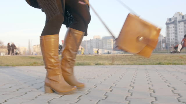 Low angle view of female legs in boots walking and purse waving around