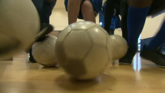 low angle view of football being kicked towards camera by primay schoolchildren during football training manchester - low angle view stock videos & royalty-free footage