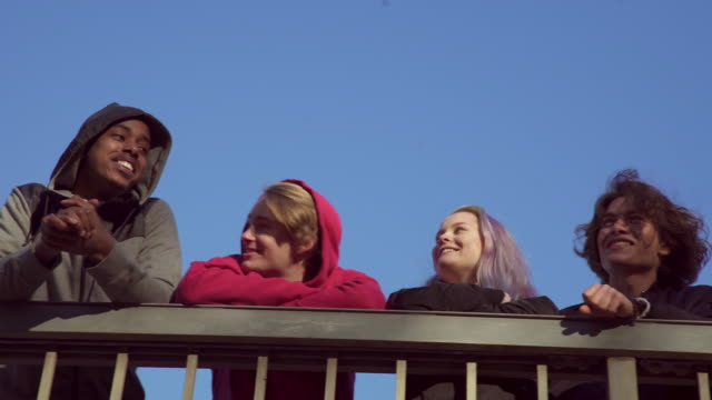 Low angle view of friends leaning on railing against clear blue sky