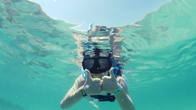 low angle view of girl snorkeling in ocean and gesturing thumbs up / tulum, quintana roo, mexico - schnorchel stock-videos und b-roll-filmmaterial