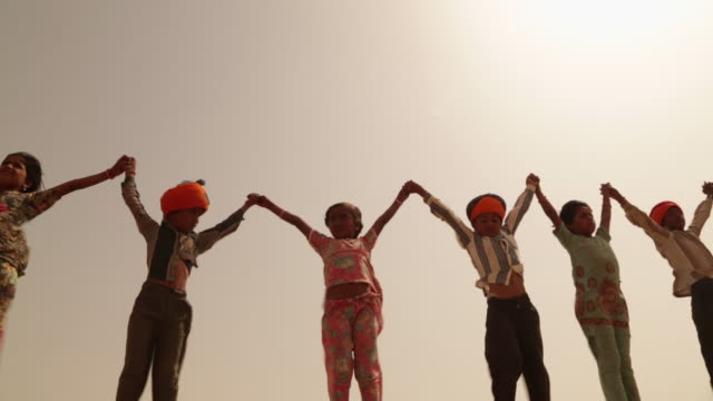 Low angle view of group of rajasthani kids holding hands, Jaisalmer, Rajasthan, India