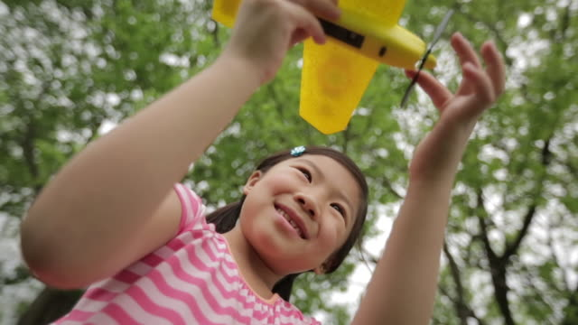 low angle view of happy girl turning propeller of toy airplane against trees - model aeroplane stock videos & royalty-free footage