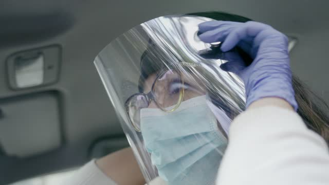 vídeos de stock, filmes e b-roll de visão de baixo ângulo da jovem hispânica montando máscara facial de dupla proteção para evitar o covid-19 - low angle view