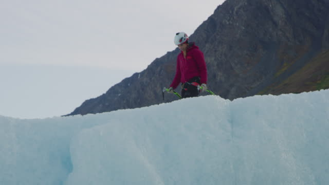 low angle view of ice climber walking on glacier carrying hooks / palmer, alaska, united states - wintermantel stock-videos und b-roll-filmmaterial