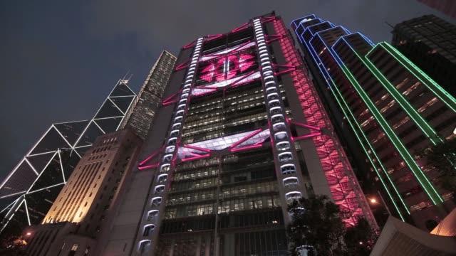 ws low angle view of illuminated flashing light of the hsbc headquarters building at night - 金融関係施設点の映像素材/bロール